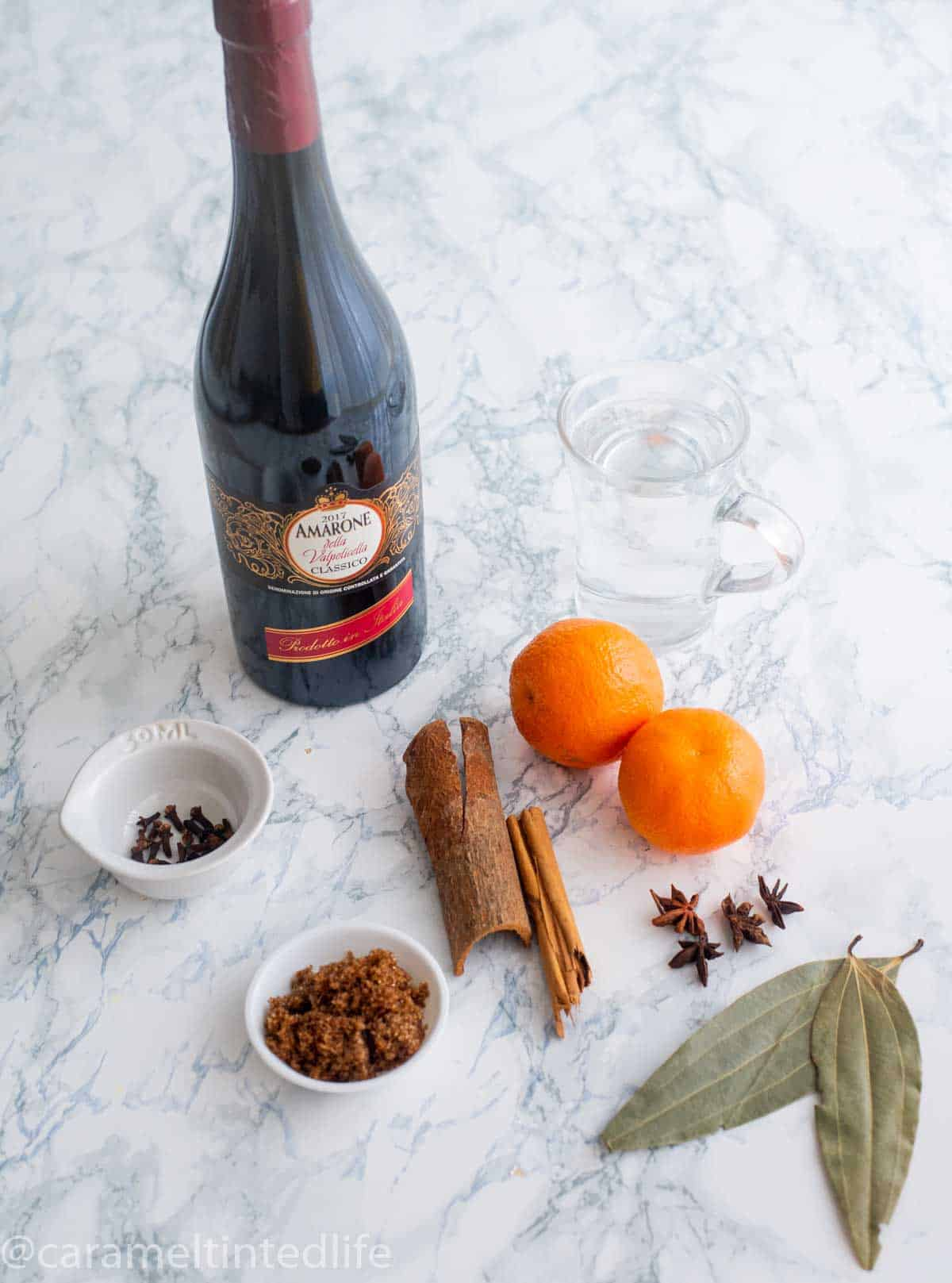 Ingredients used to make mulled wine, on a white surface