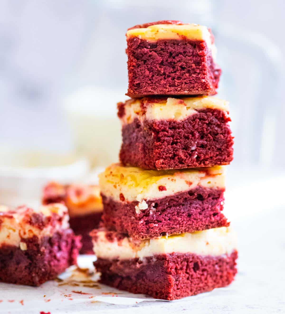 A stack of four red velvet and cheesecake brownies in the foreground, a milk jug in the background