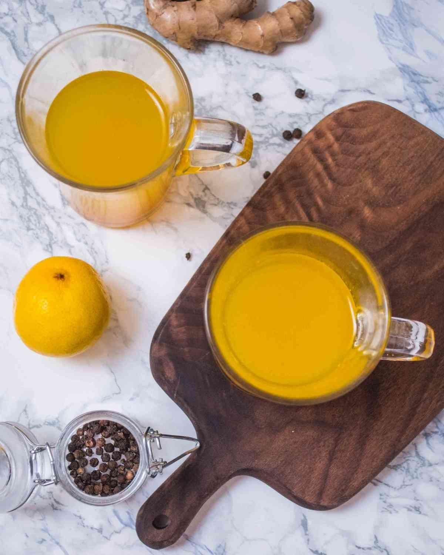 Two glasses on ginger lemon tea, served on a wooden board