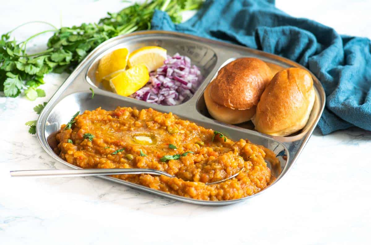 A steel plate with pav bhaji, onions and lemon in the foreground