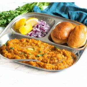 Pav bhaji on a plate served with onions and lemon and coriander garnish