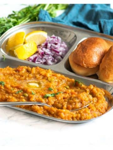 Pav bhaji on a plate served with onions and lemon and coriander garnish