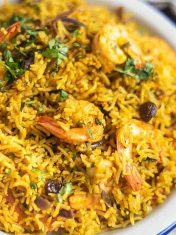 Close up of shrimp biryani on a white plate