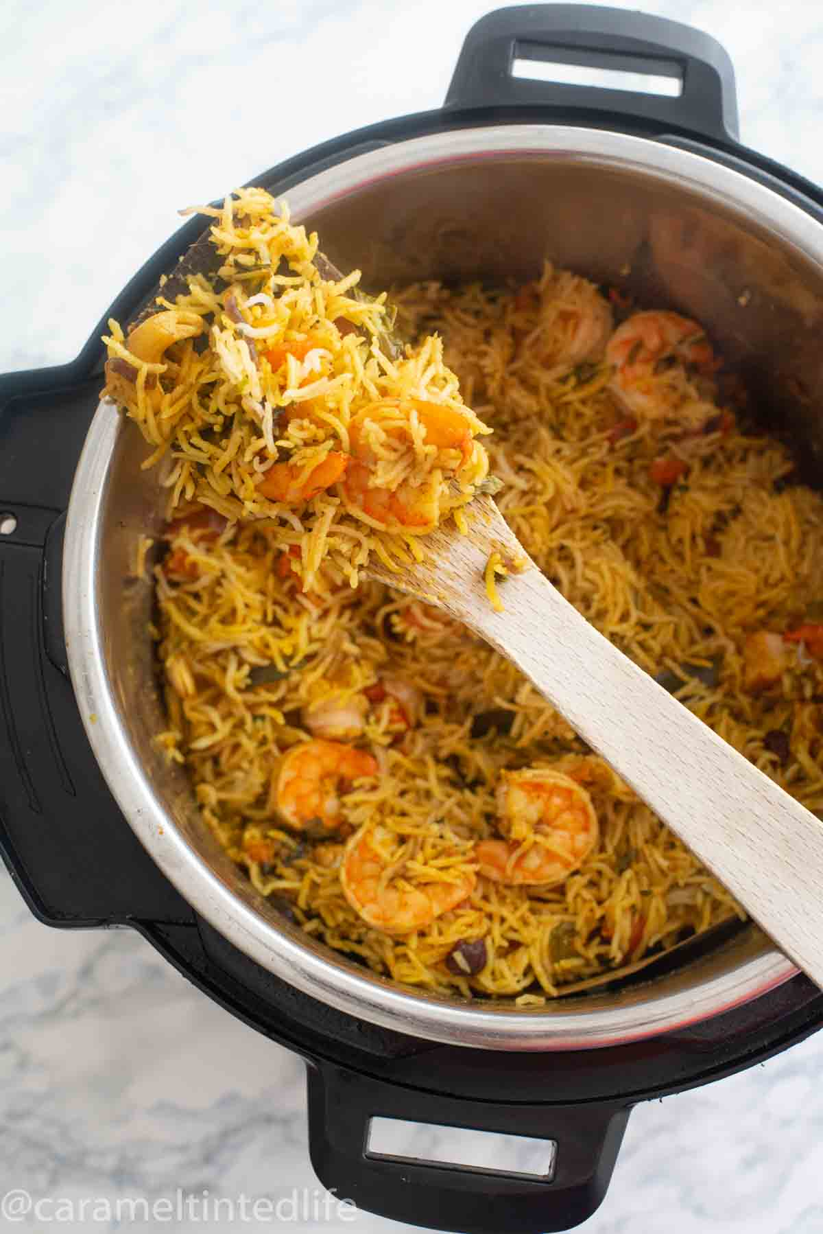 Shrimp biryani on a wooden ladle resting on an Instant Pot