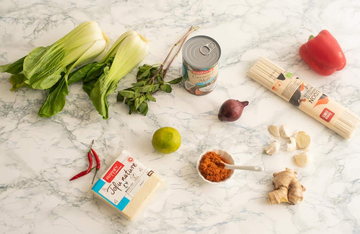 Ingredients used to make Thai Noodle soup including udon noodles, Thai curry paste, etc.