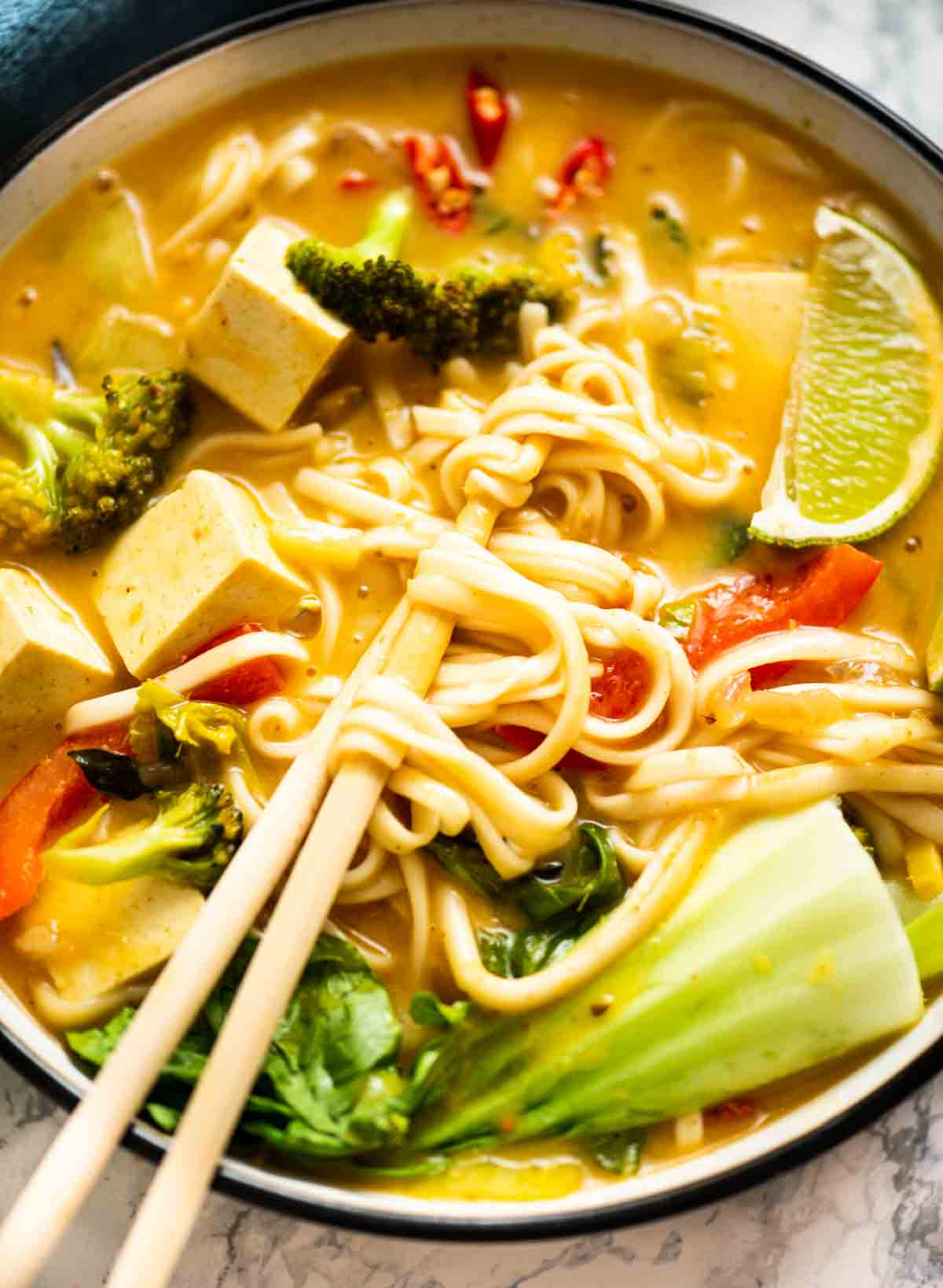 Close-up of a bowl of noodle soup with chopsticks pulling the noodles