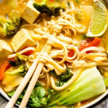 Close up of chopsticks holding noodles in a soup bowl