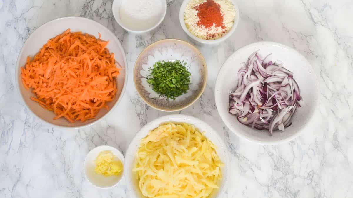 All ingredients to make pakoras including sliced vegetables and gram flour
