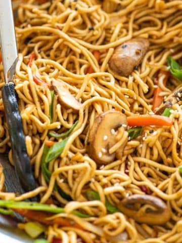 Vegetable Chow Mein scooped up with tongs