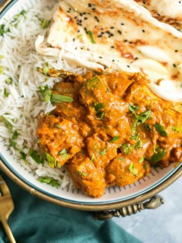 bowl of chicken in a thick sauce, with naan and rice