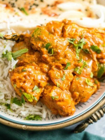 chicken kadai in a bowl with rice and naan