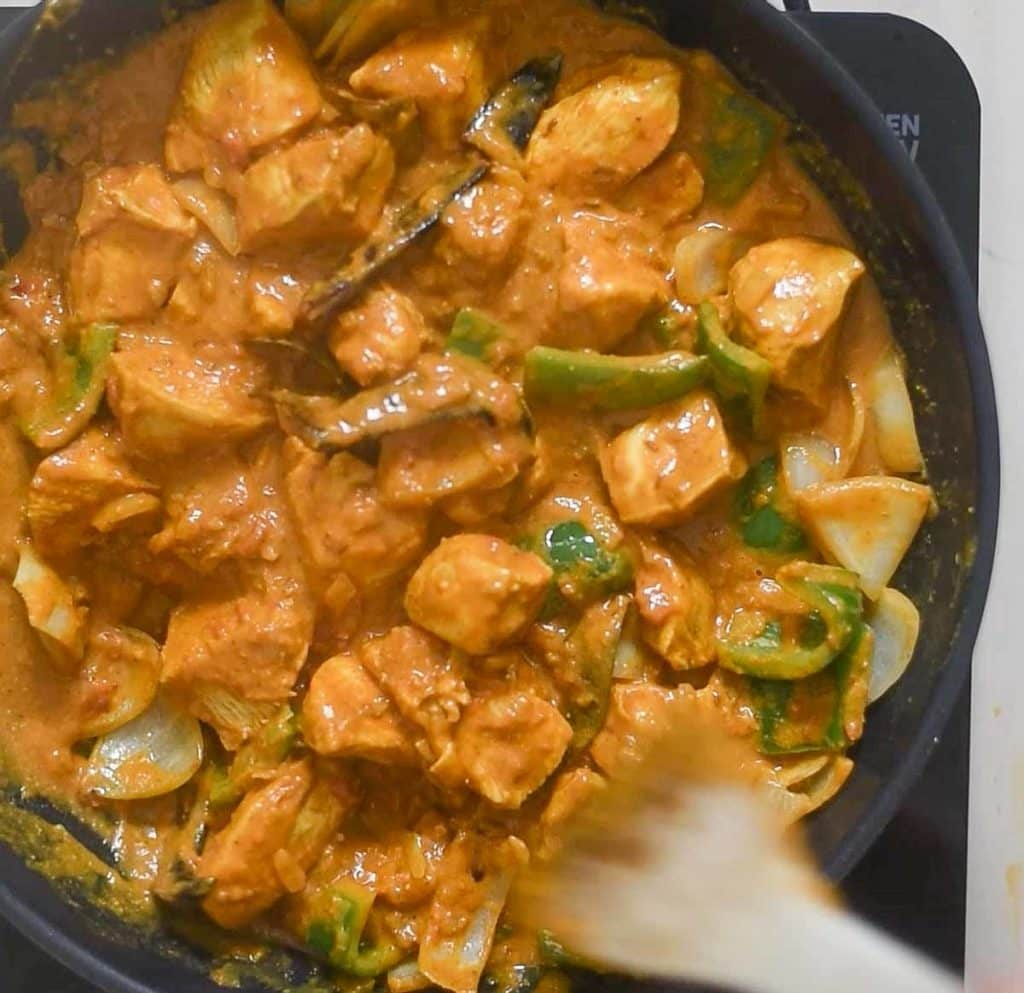 Addition of chicken to sauteed bell pepper and onion