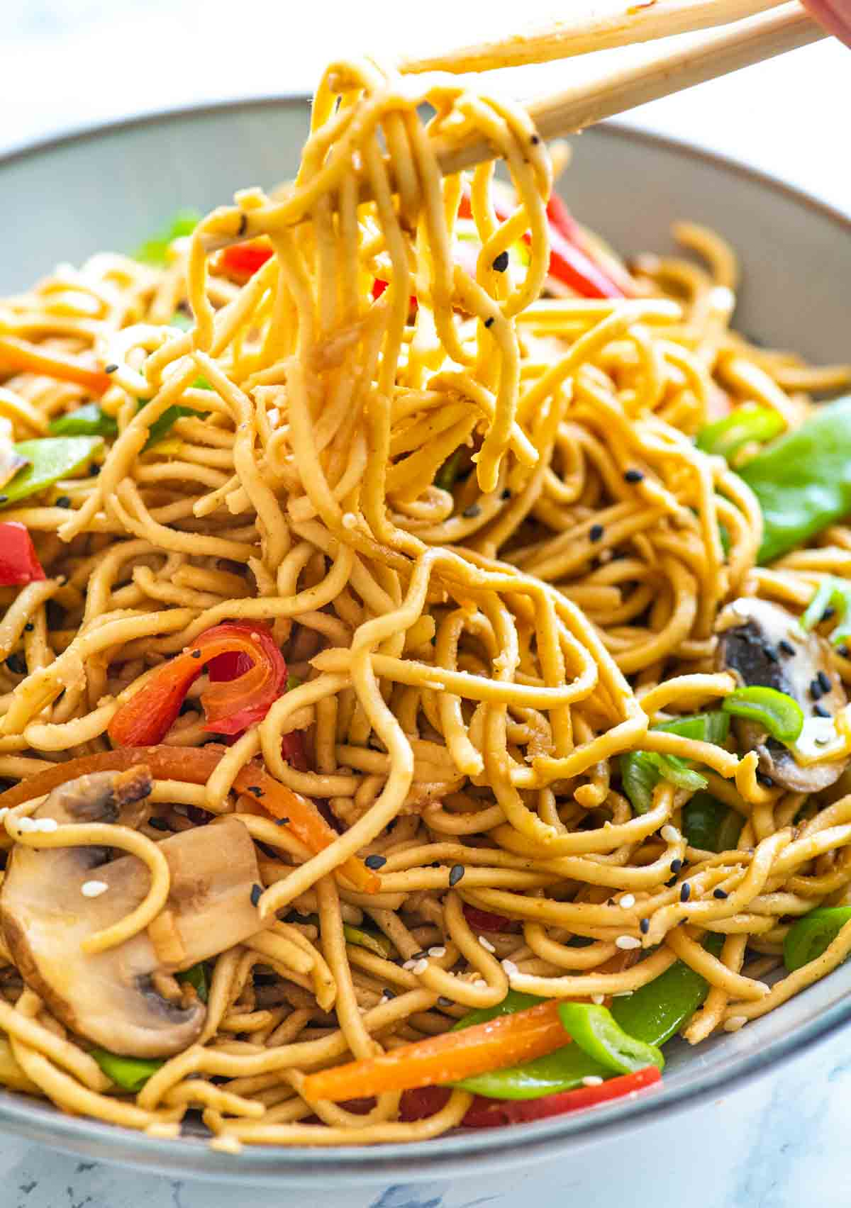 Chopsticks lifting up vegetable chow mein noodles in a bowl