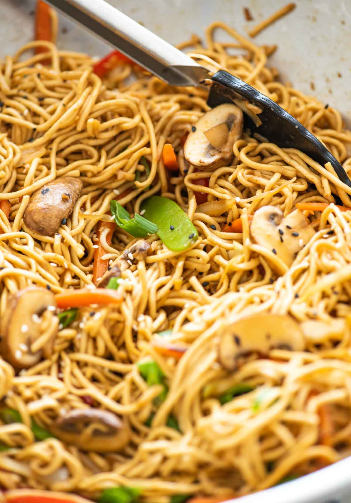 Vegetable chow mein in a wok, mixed with tongs