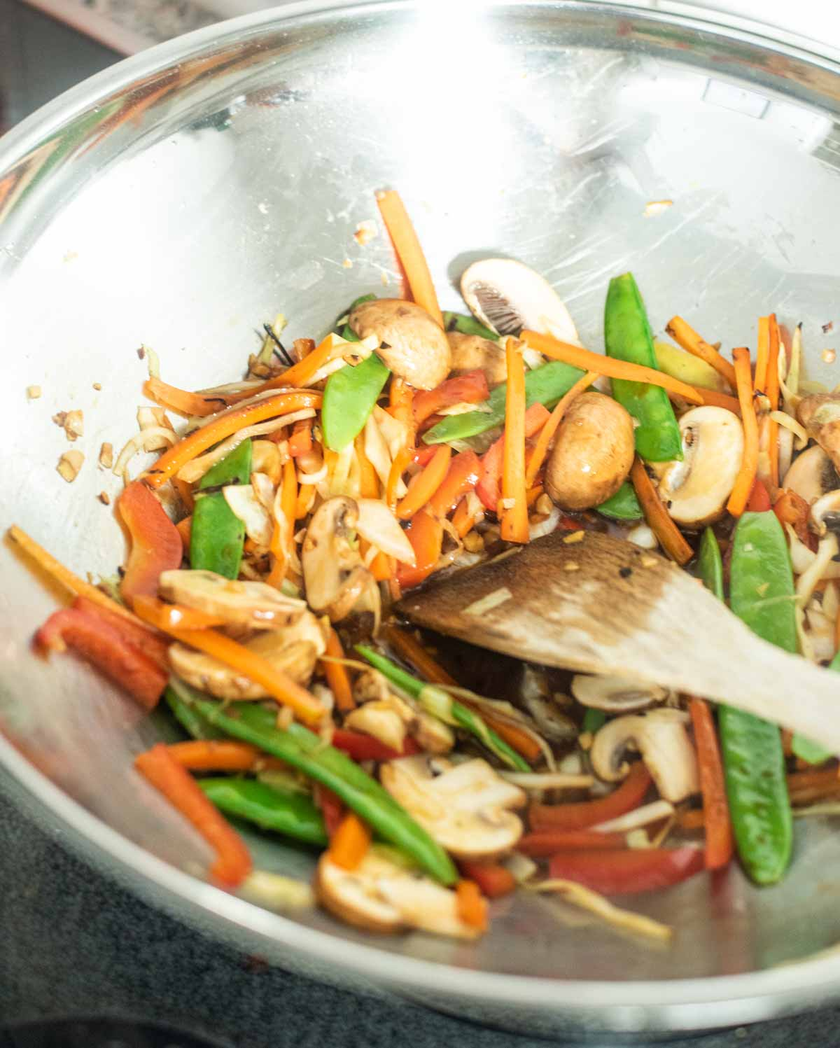 Vegetables being stir fried in a wok with a wooden spatula