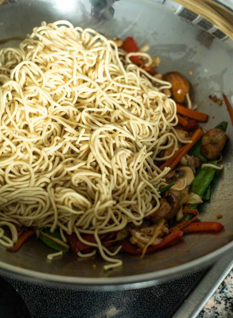 Cooked noodles are added to a wok with stir fried vegetables