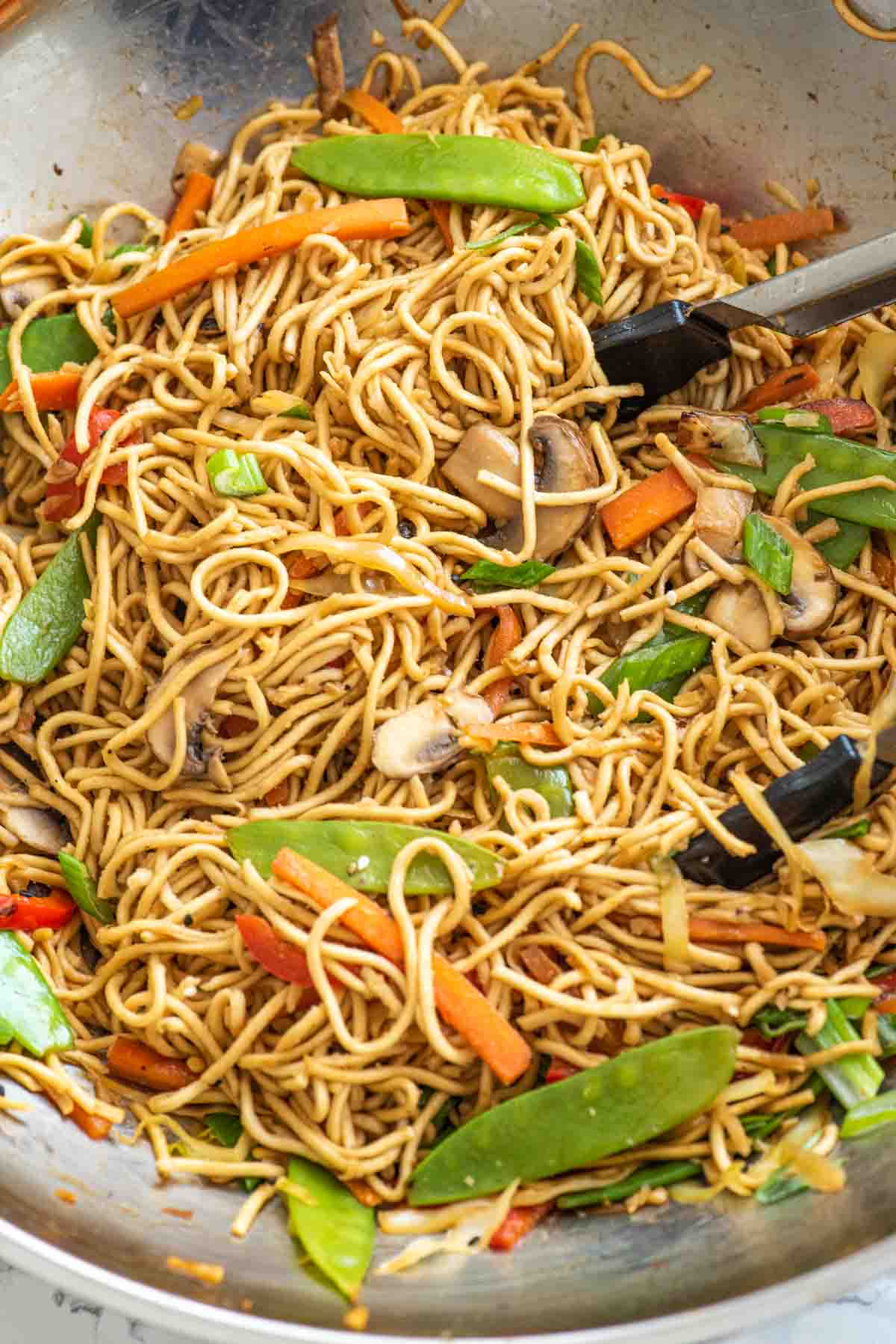 Stir-fried noodles are tossed together in a wok with a pair of tongs