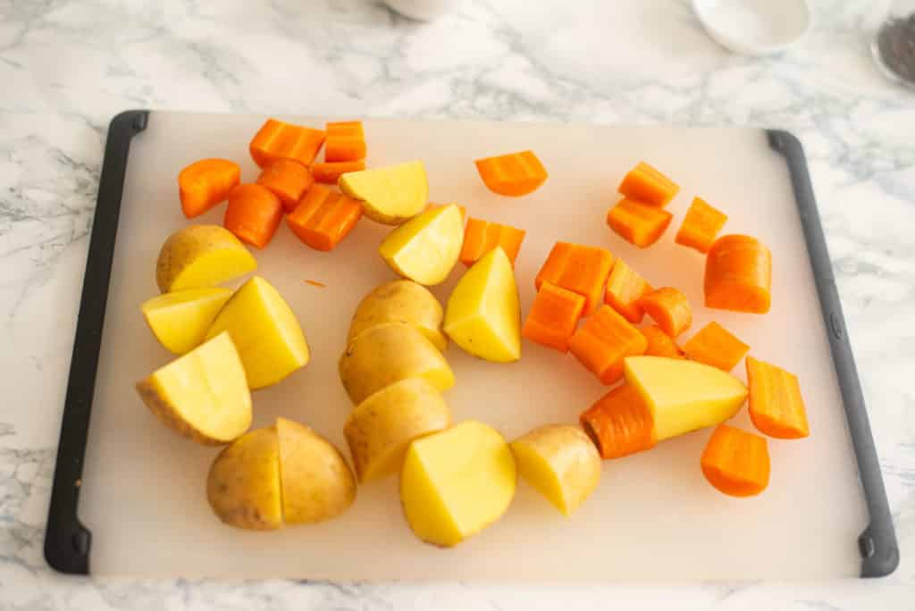 chopped potatoes and carrots on a chopping board