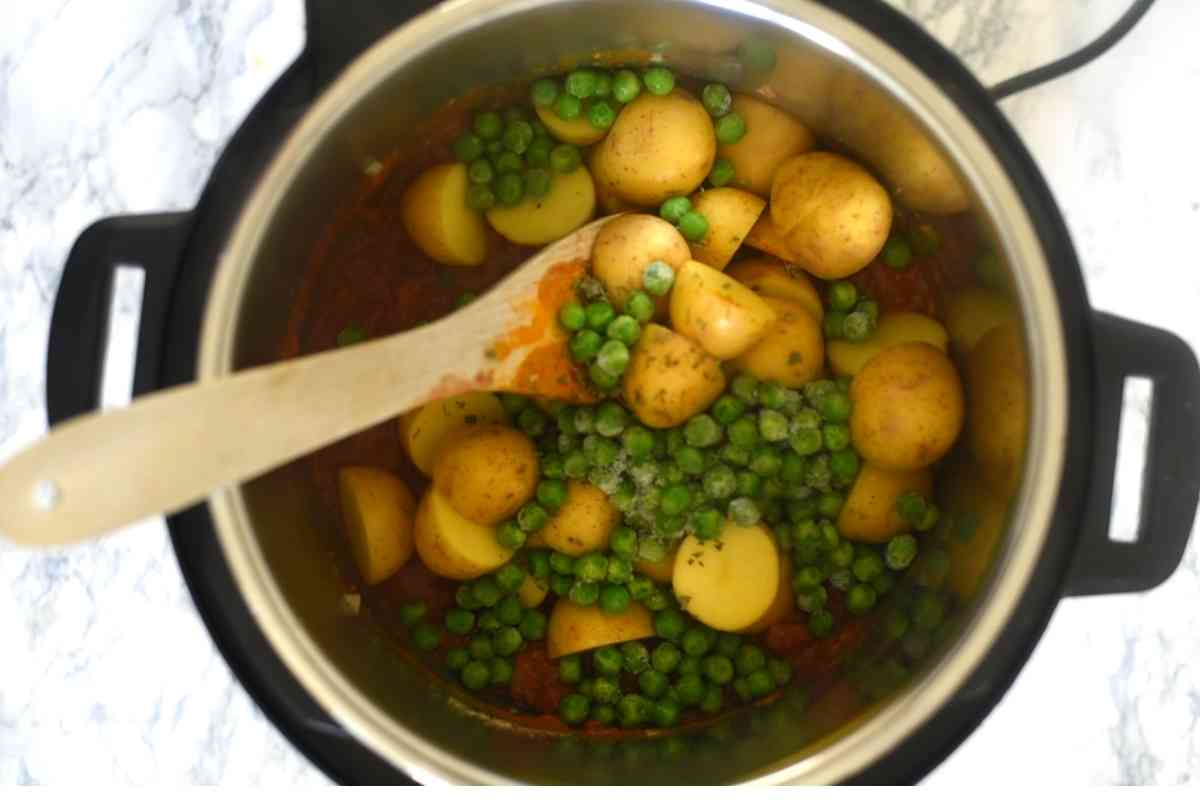 Instant Pot with potatos, peas and a wooden spatula