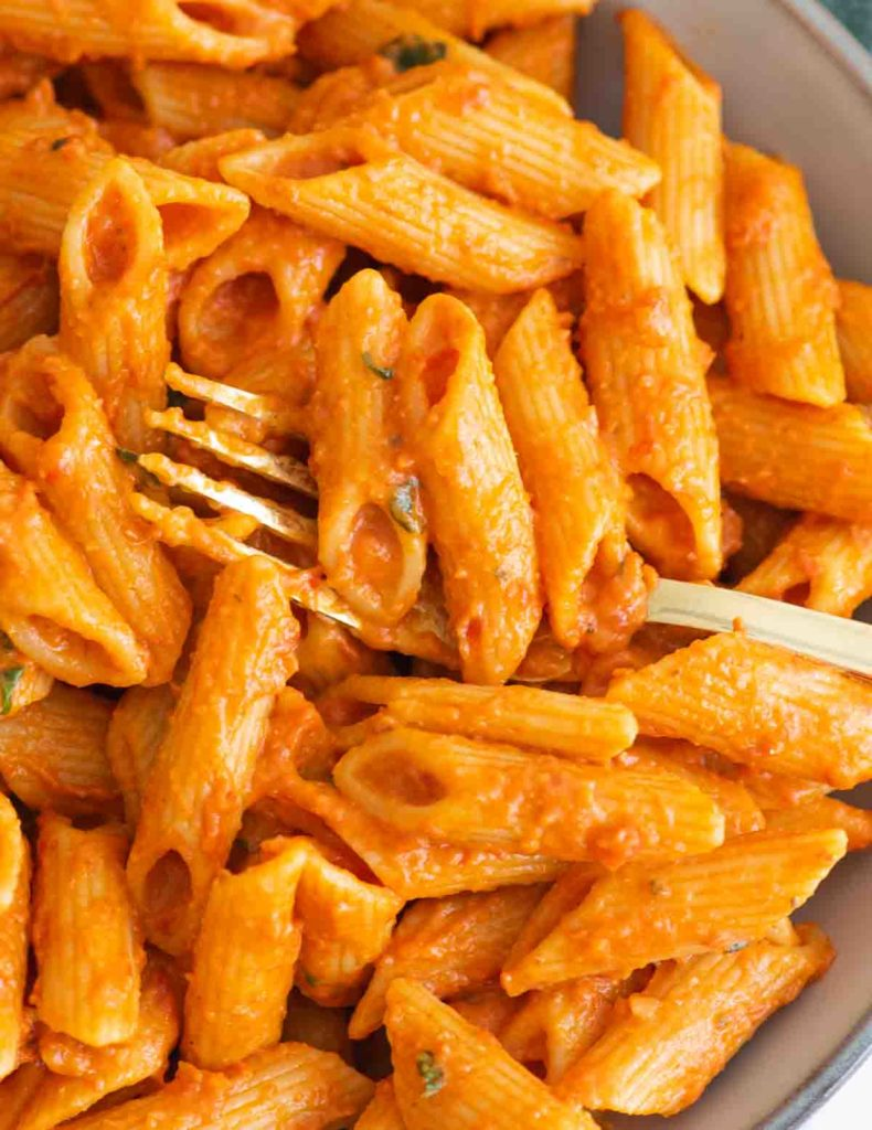 Closeup of a fork in a bowl of creamy penne pasta