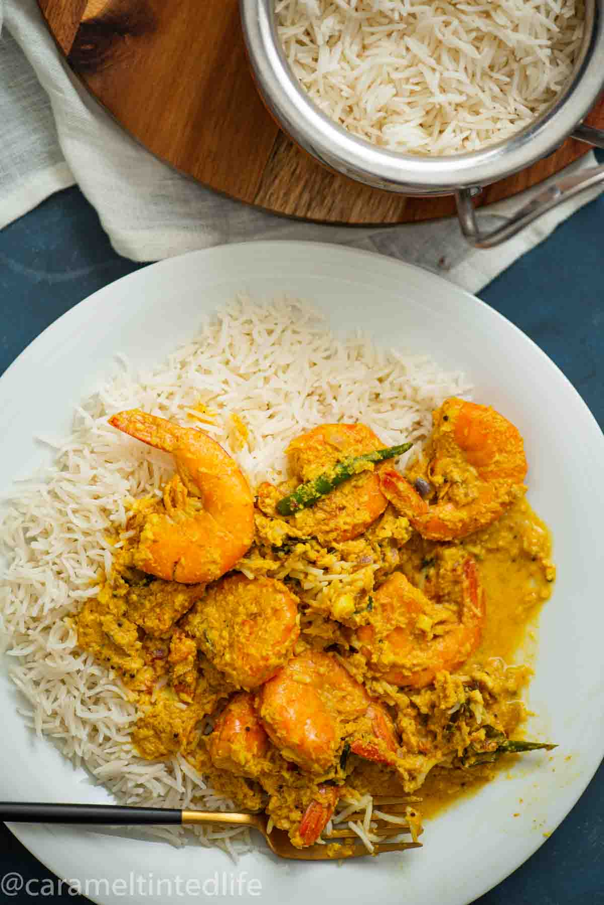 plate of white rice with shrimp curry and a fork