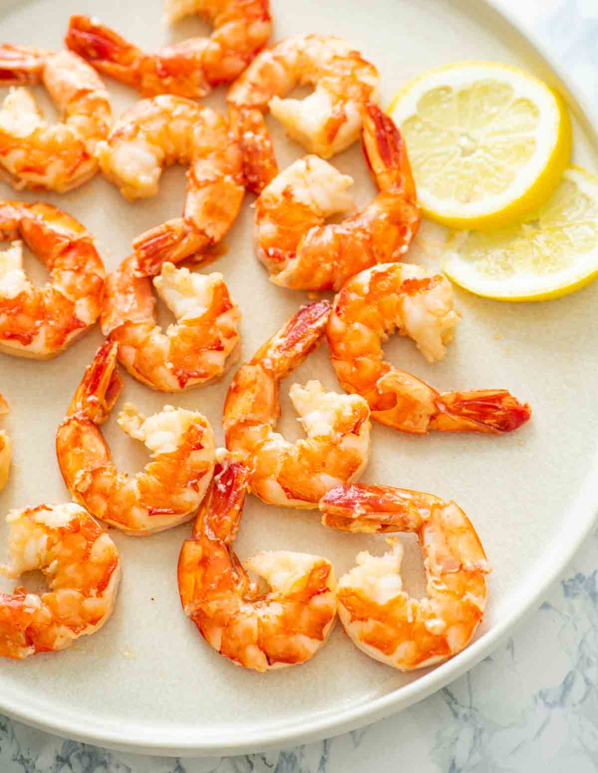 cooked shrimp with tails on and lemon slices on a white plate