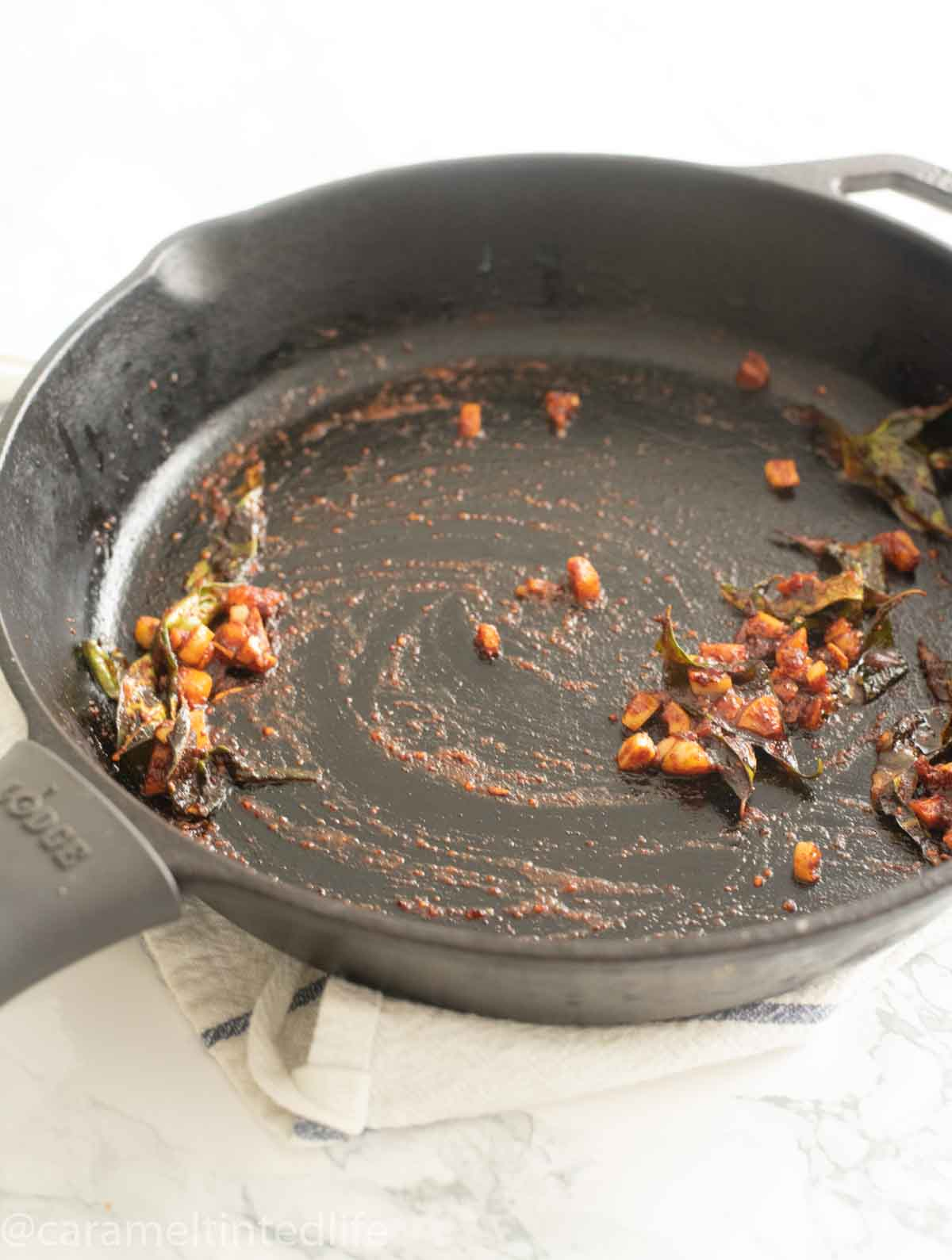 chili, garlic and curry leaves in a cast iron pan