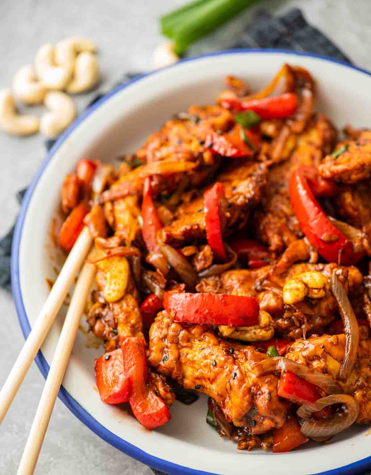 chicken with bell pepper served on a white plate with chopsticks