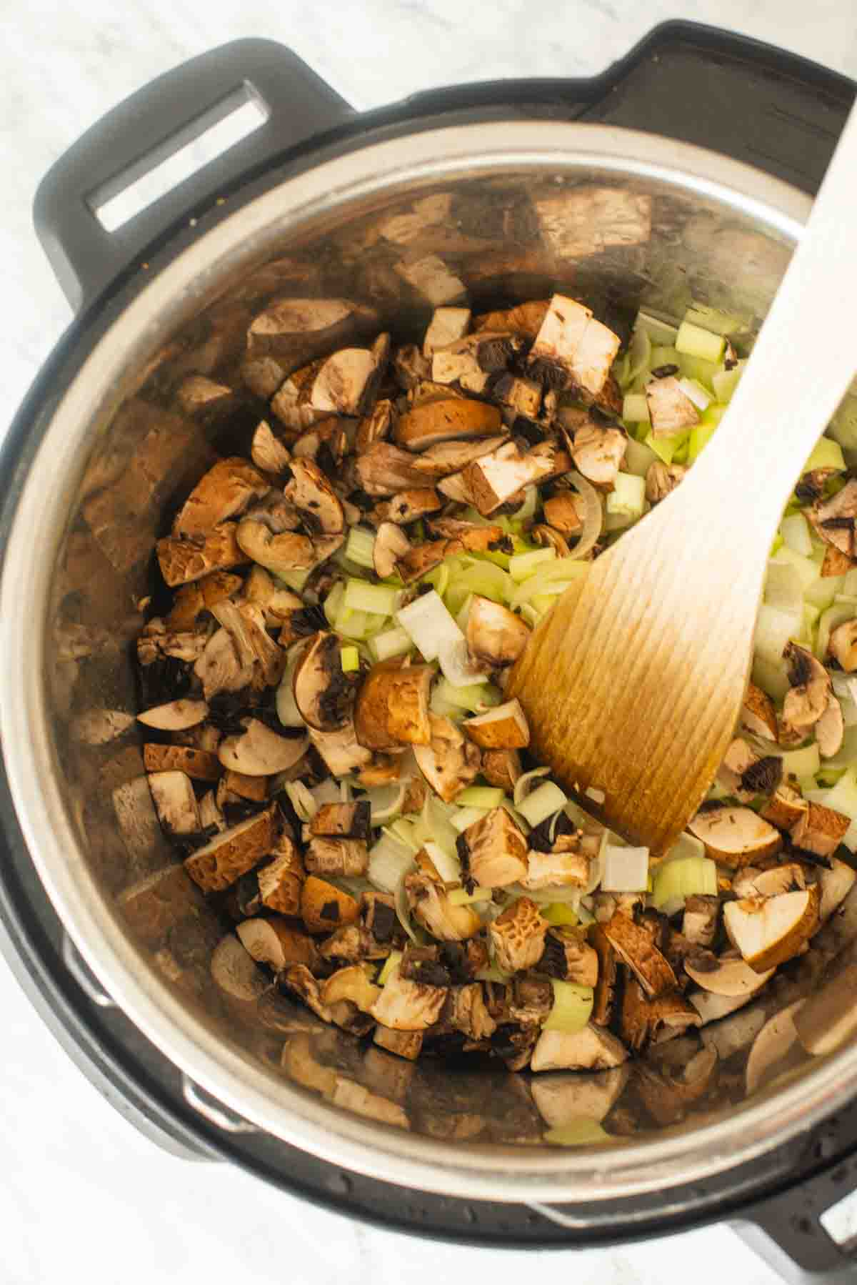 Chopped leeks, mushrooms inside an Instant Pot