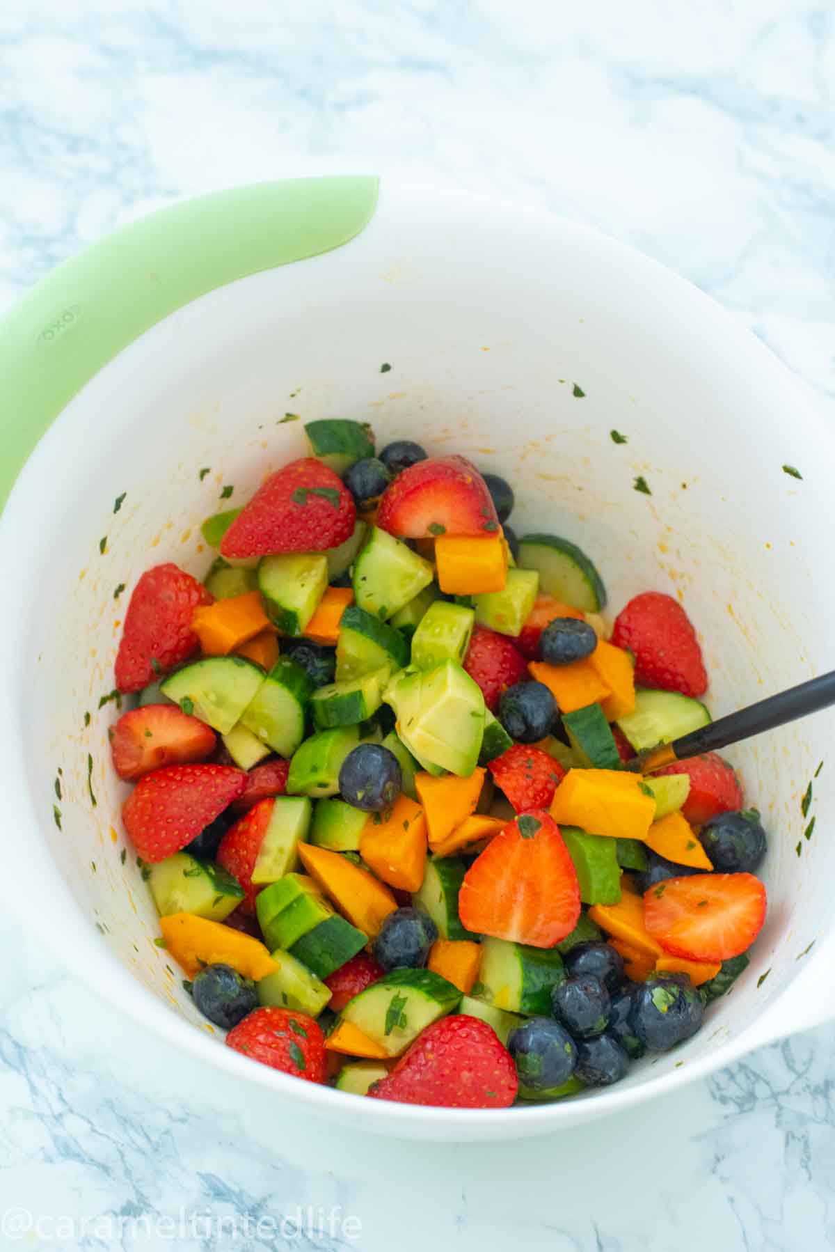fruits and salad dressing getting mixed in a bowl