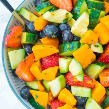 A spoon dipping into a bowl of fruit salad