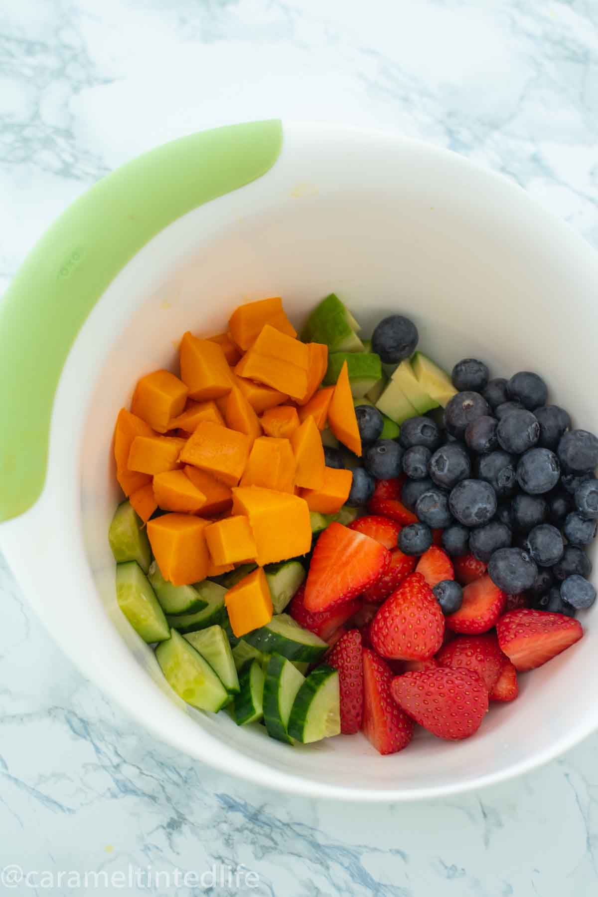 Mangoes, cucumber, avocado and berries in a large mixing bowl