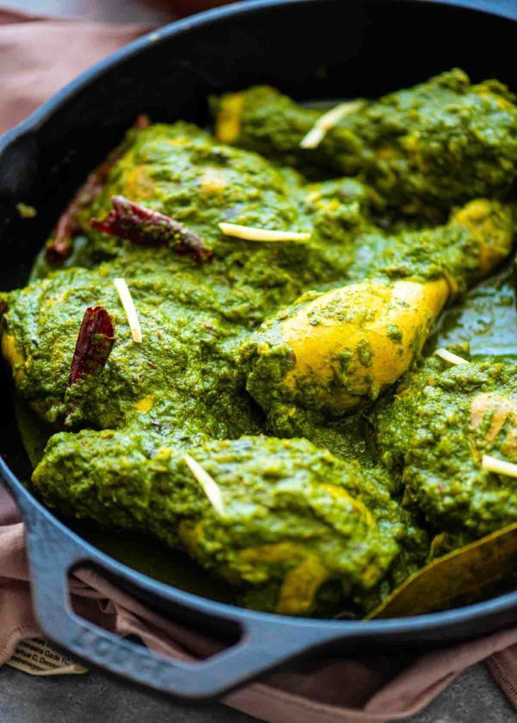 Side view of green chicken curry in a black cast iron pan