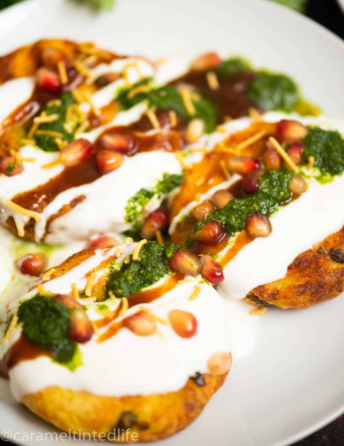 tikkis on a plate with sauces and chutneys