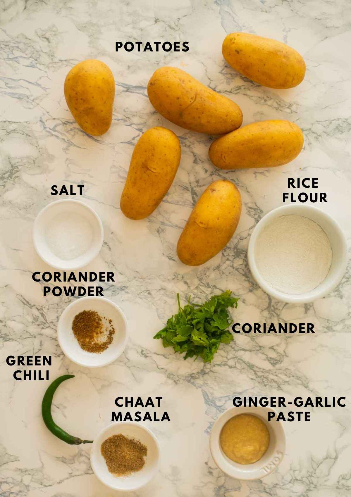 All the ingredients for making aloo tikki placed on a white board