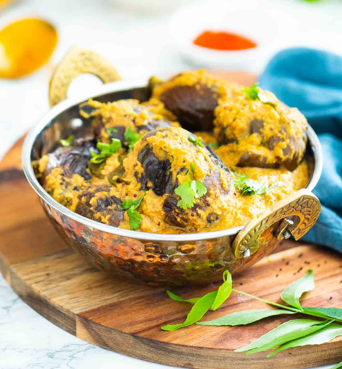 baby brinjal curry served in a copper dish on a wooden board