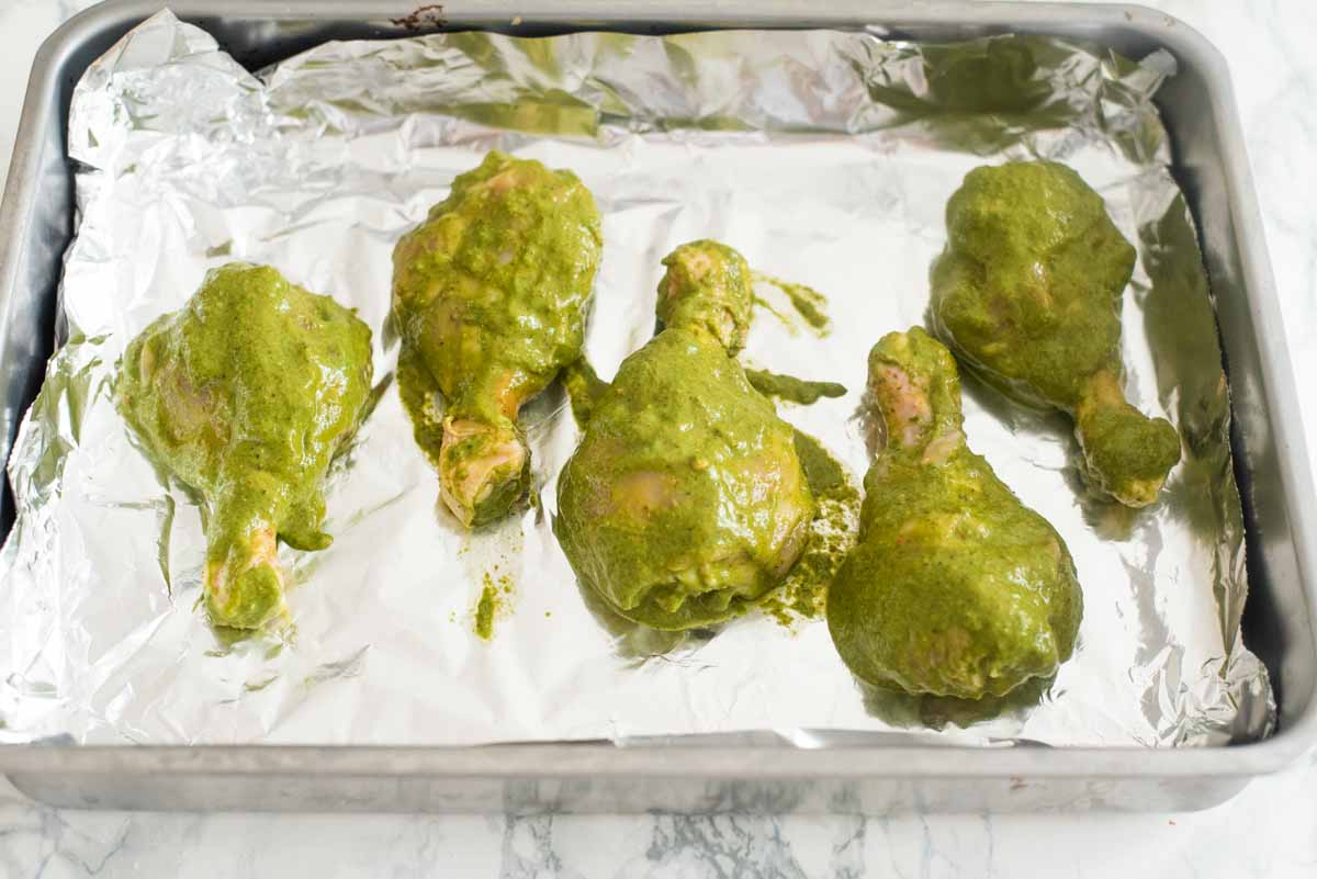 Chicken legs in a green marinade on a foil sheet on a baking dish