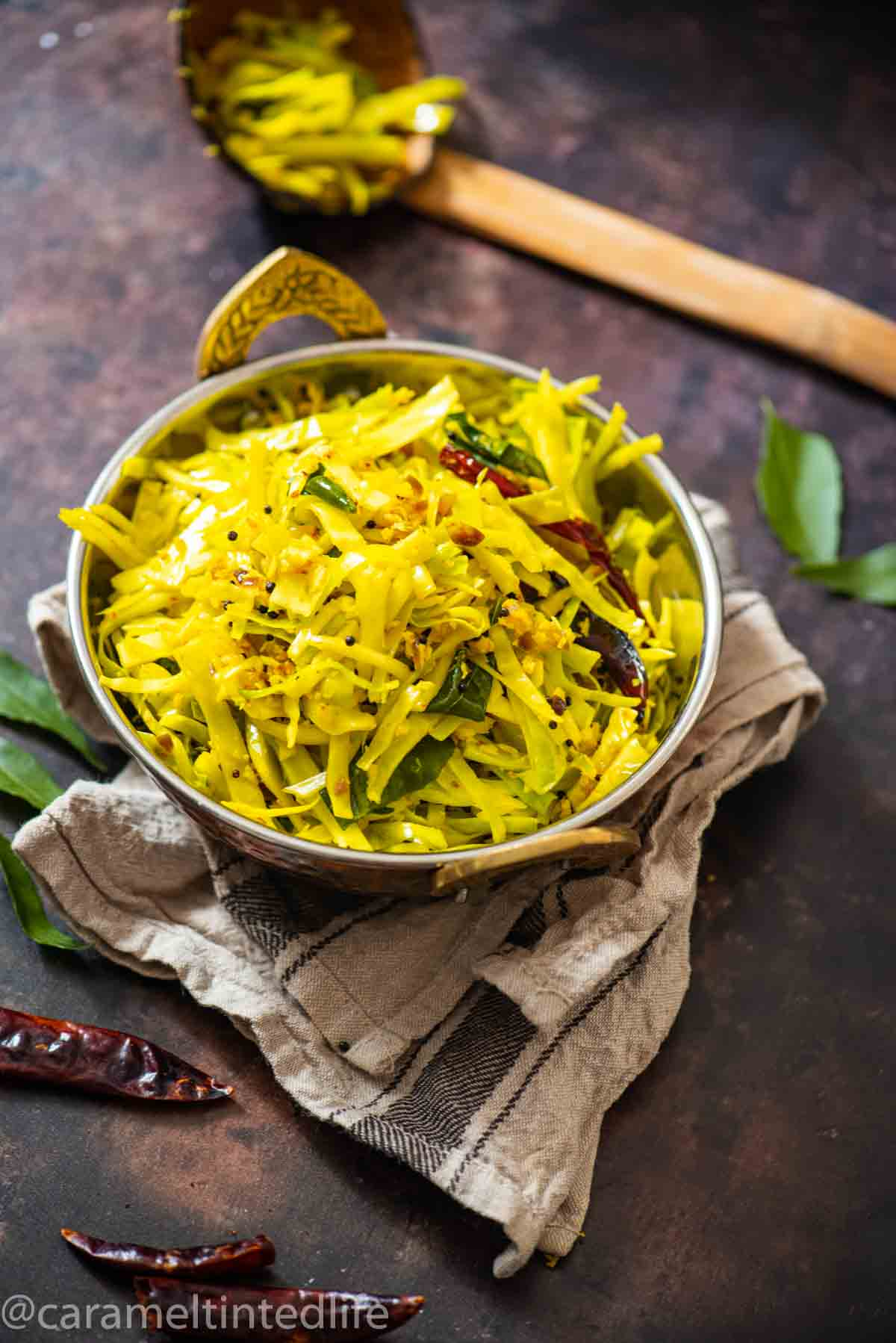 serving bowl with sauteed cabbage on a brown background