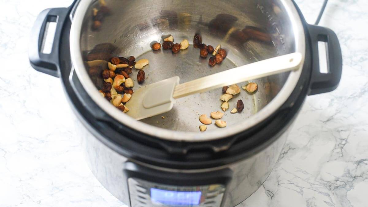 Instant Pot with raisins and cashews and a splatula