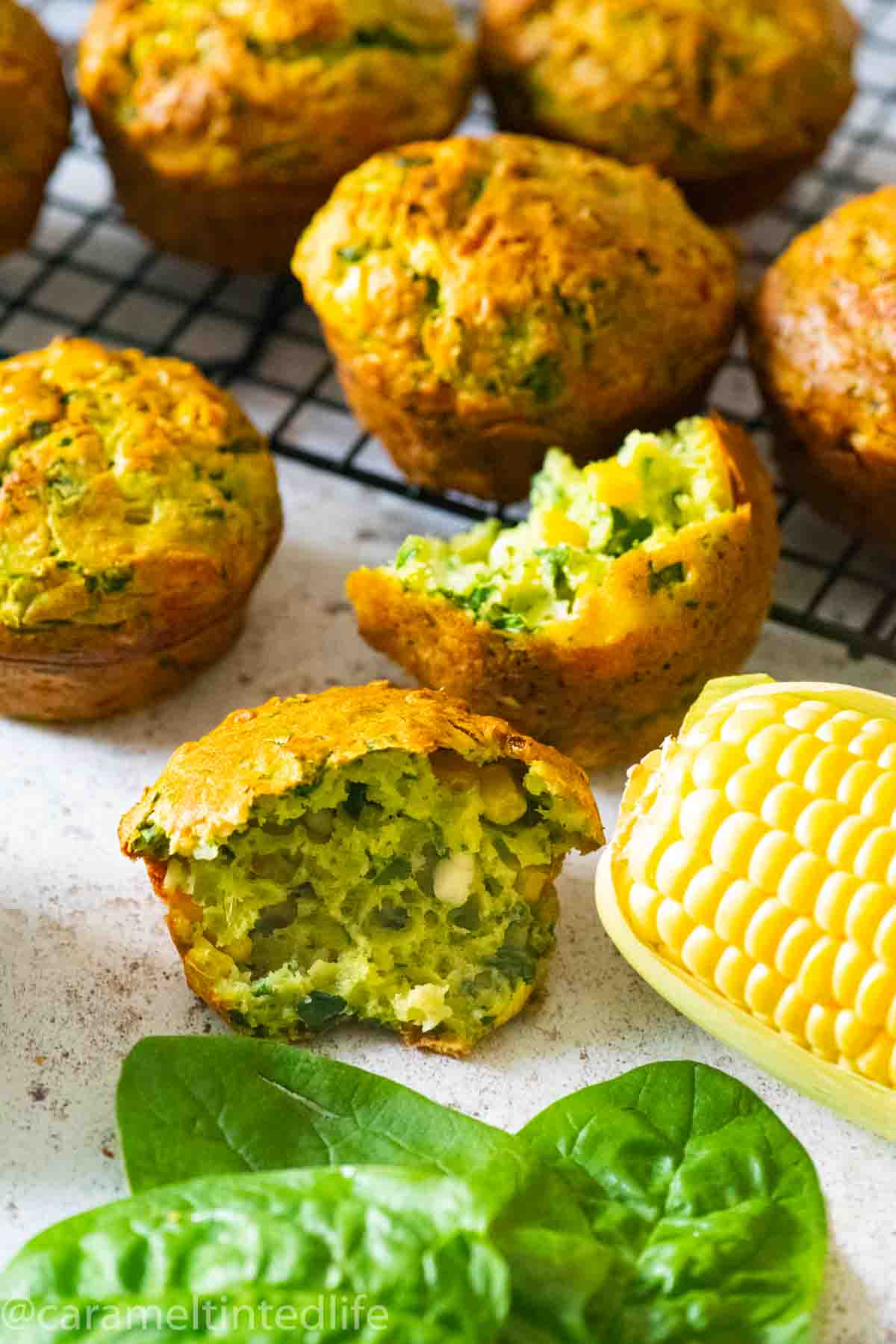 a broken spinach muffin with a corn cob and spinach leaves