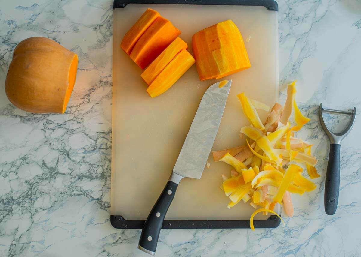 chopping board with knife and butternut squash pieces