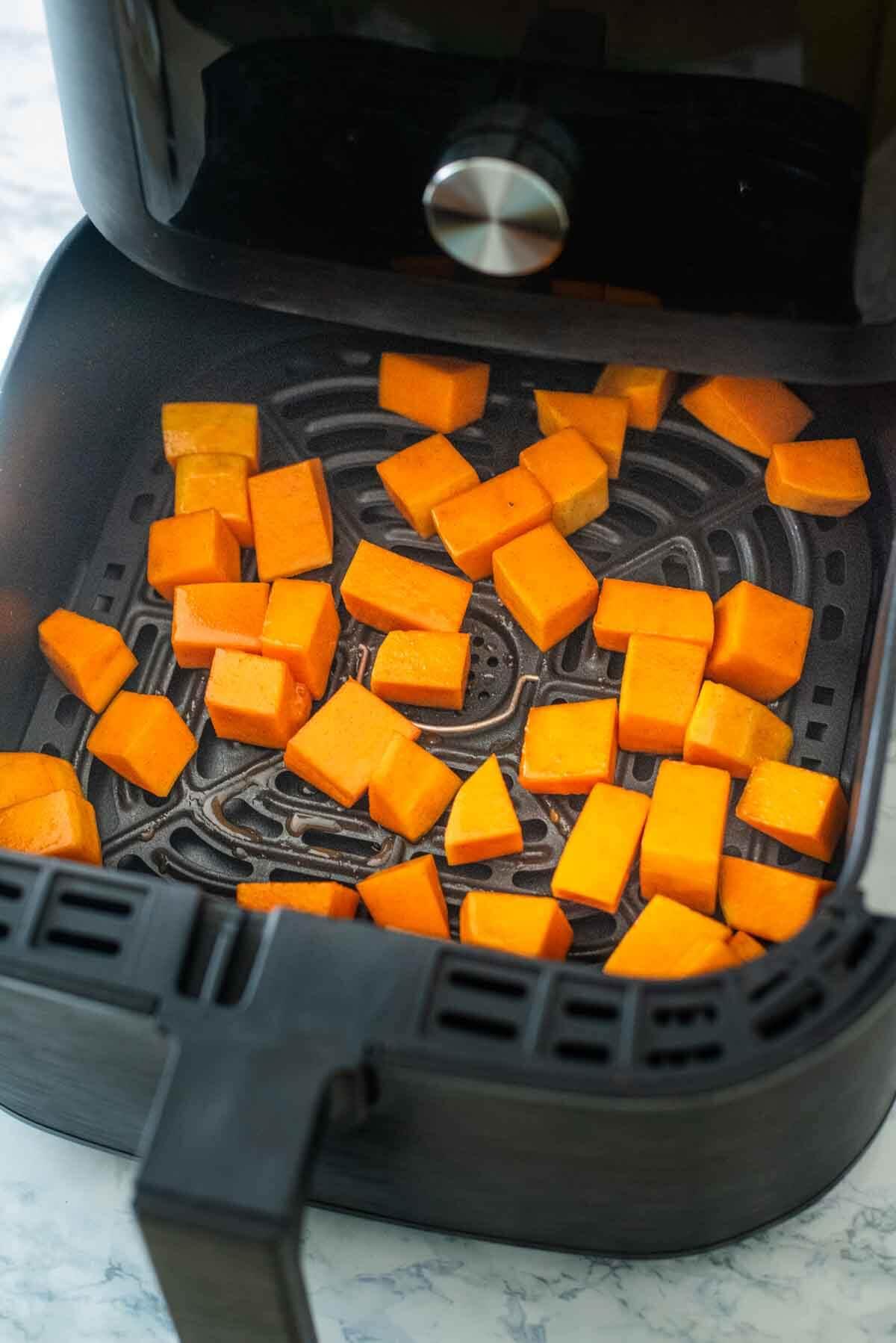 butternut squash pieces in an air fryer