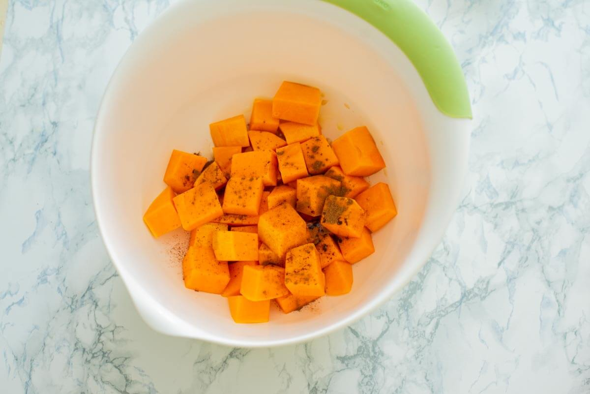 mixing bowl with butternut squash pieces with cinnamon powder