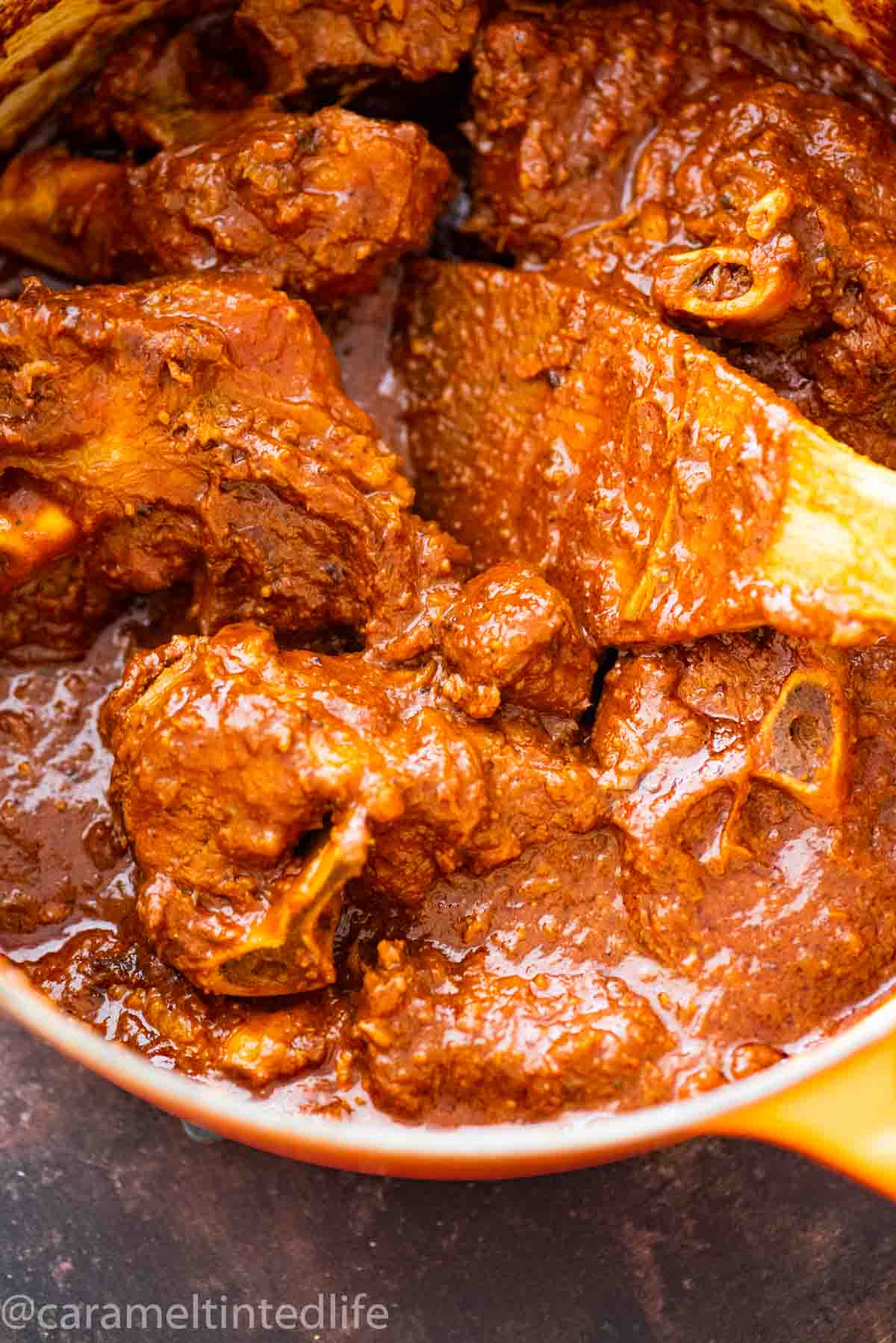 lamb curry in a dutch oven with a wooden spatula