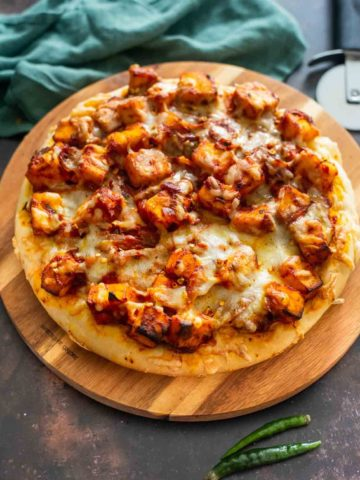 round pizza with paneer and tomato sauc etopping on a wooden board