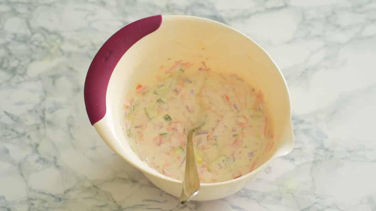 mixing bowl of yogurt mixed with veggies