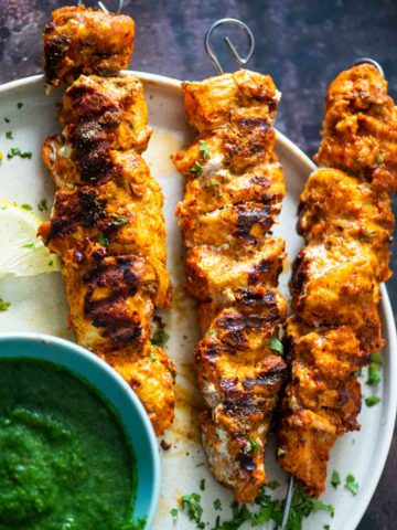 three skewers of grilled chicken tikka