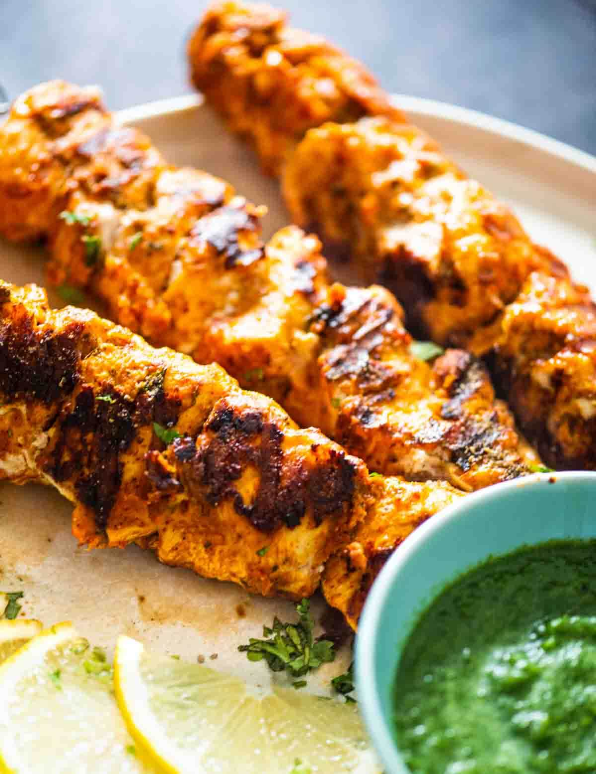grilled chicken with green chutney and lemons on a plate