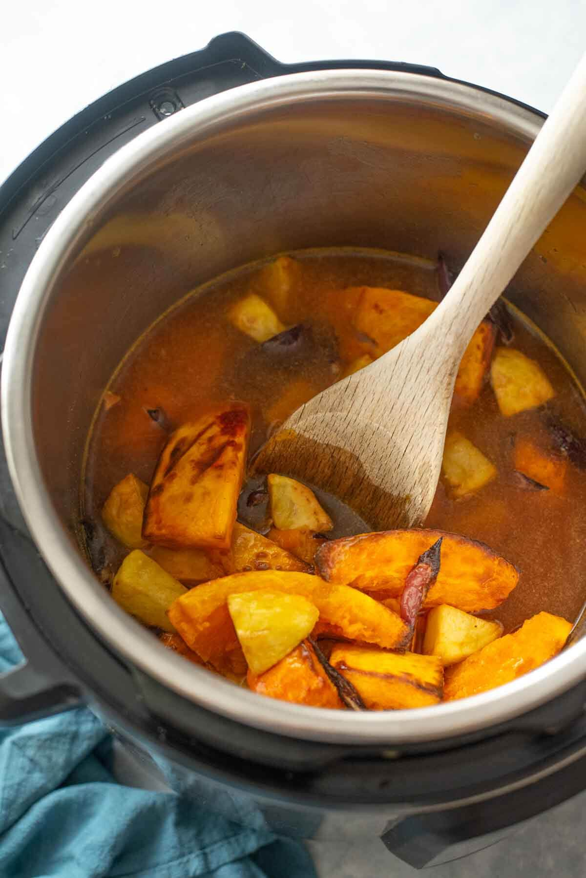roasted veggies and stock in an instant pot with a spatula