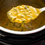 ladle holding palak dal over an instant pot
